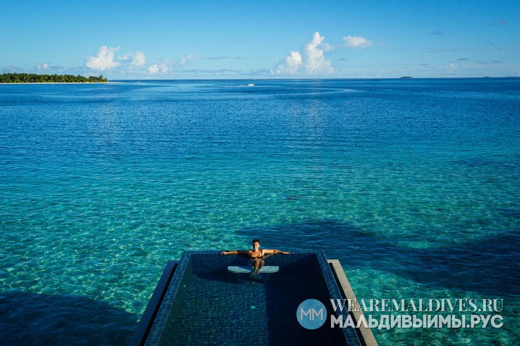 Девушка в панорманом бассейне водной виллы мальдивского отеля Angsana Velevaru