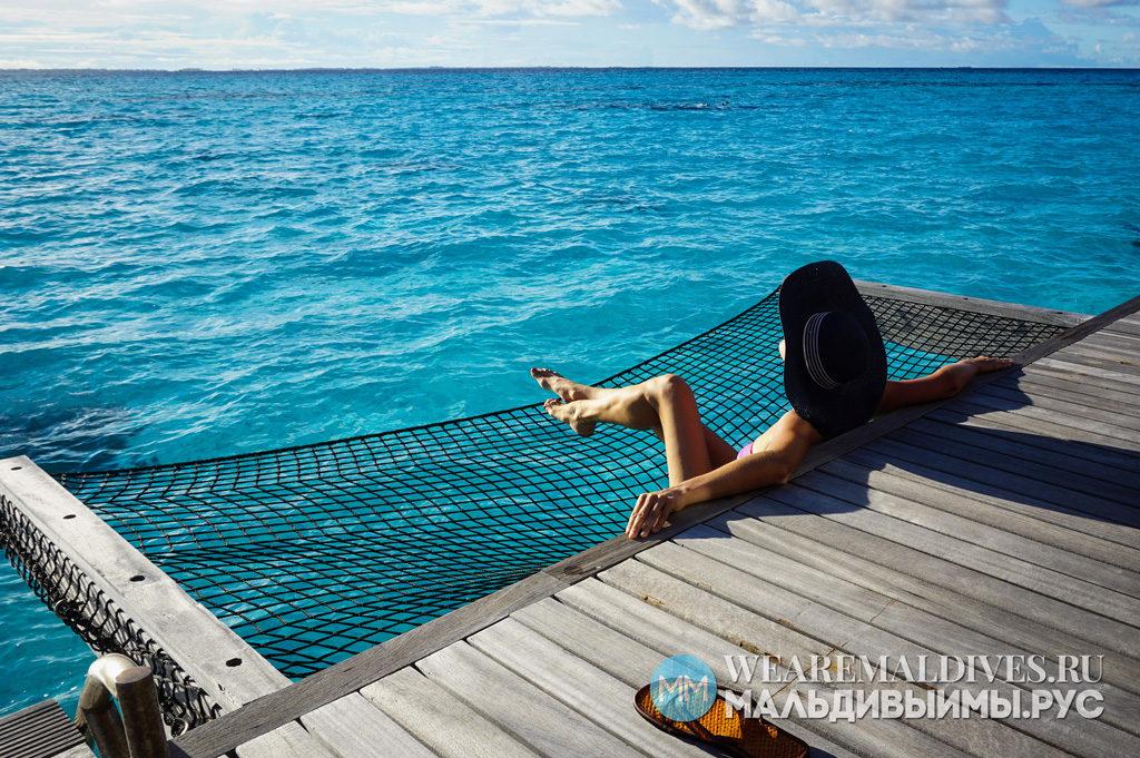 Девушка загорает в водной вилле отеля Shangri-La Maldives
