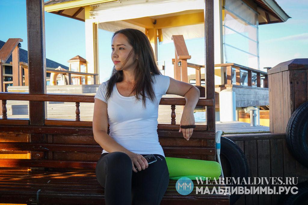 Девушка в лодке дхони в лагуне острова Angsana Velavaru