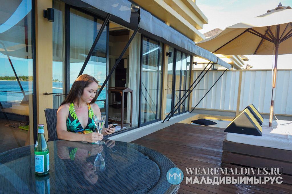 Девушка на террасе водной виллы отеля Angsana Velavaru Maldives