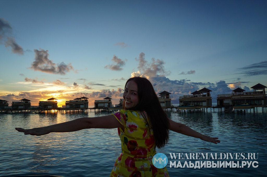 Девушка на фоне заката и водных вилл отеля Ангсана Велавару Мальдивы