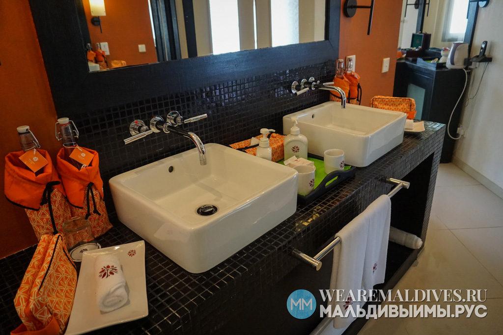 Раковины и зеркало внутри номера пляжной виллы отеля Angsana Velavaru в Мальдивах