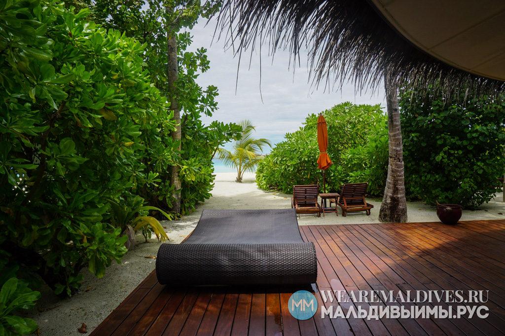 Терраса и личный пляж с шезлонгами на пляжной вилле мальдивского острова отеля Angsana Velavaru