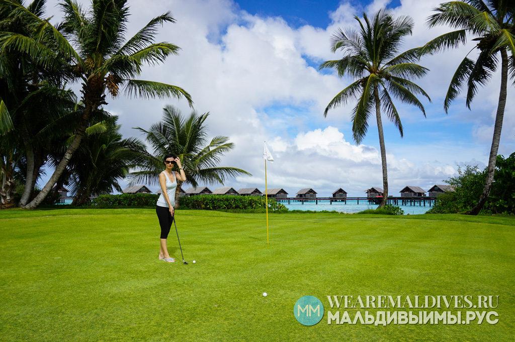Девушка на поле для гольфа острова отеля на Мальдивах