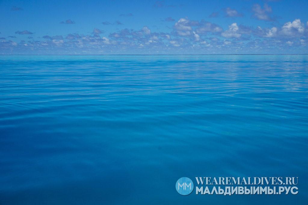 Голубая вода Индийского океана Мальдив под облаками в небе