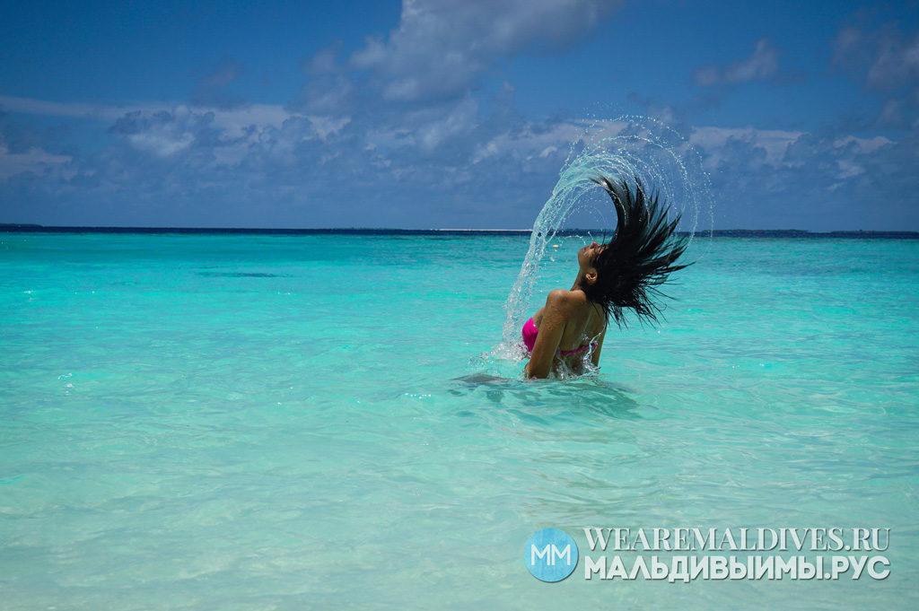 Девушка в купальнике в прозрачной воде Индийского океана в отеле Soneva Fushi