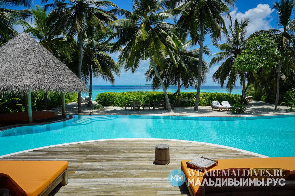 Зона отдыха с бассейном, личным пляжем, пальмами и видом на океан на вилле острова-отеля Soneva Fushi