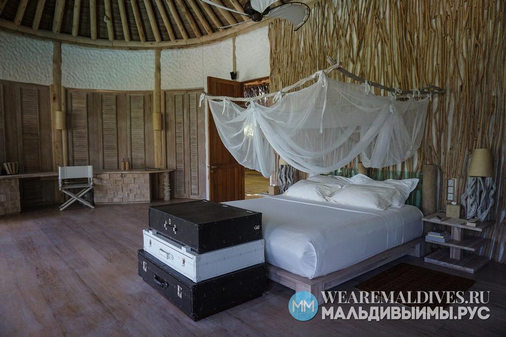 Кровать в спальне внутри виллы в Soneva Fushi