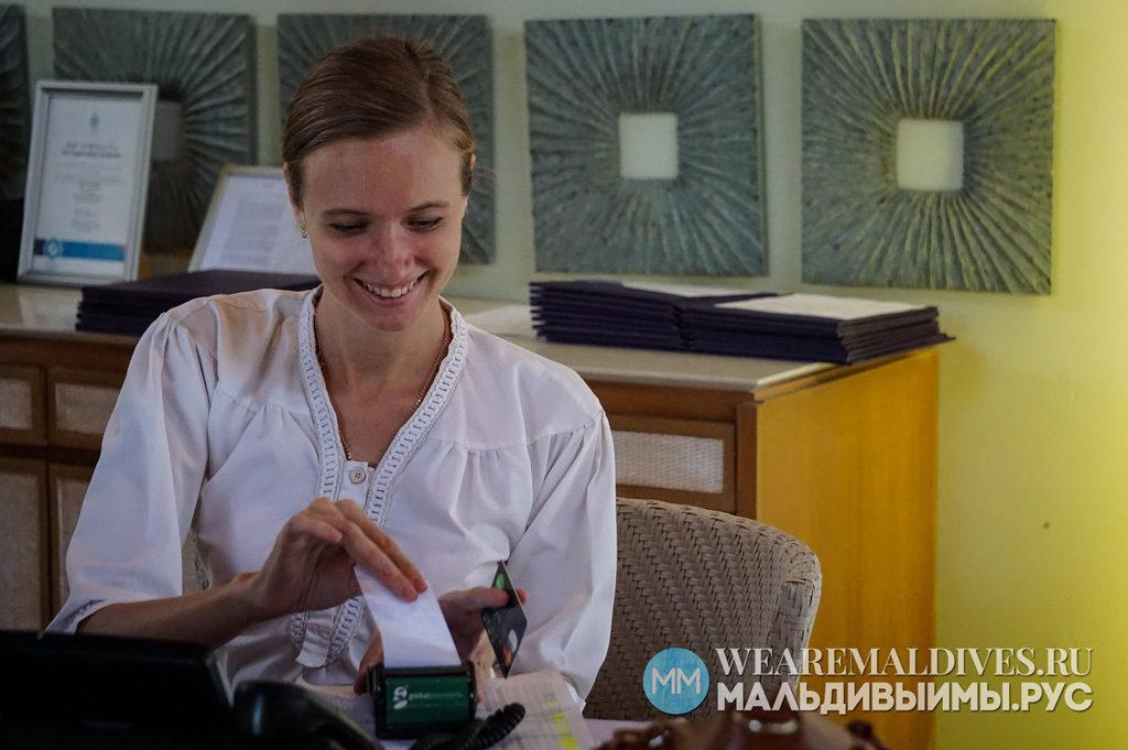 Работница отеля Dusit Thani принимает оплату банковской карточкой