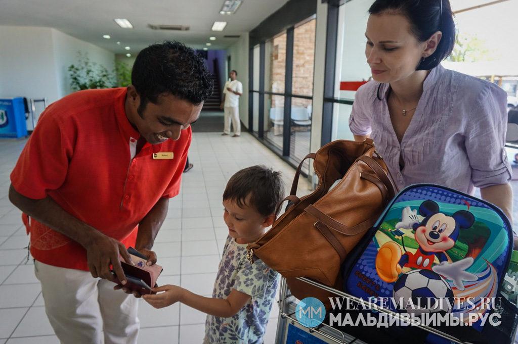 Представитель мальдивского отеля помогает госятм с регистрацией на внутренний рейс мальдивских авиалиний