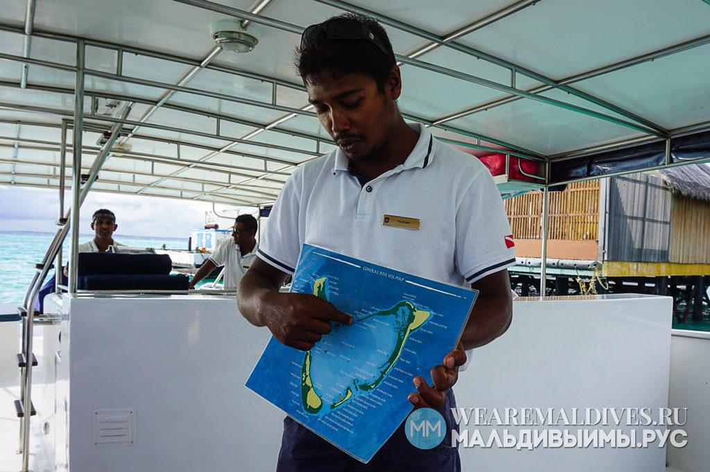 Работник отеля Shangri-La показывает карту атолла