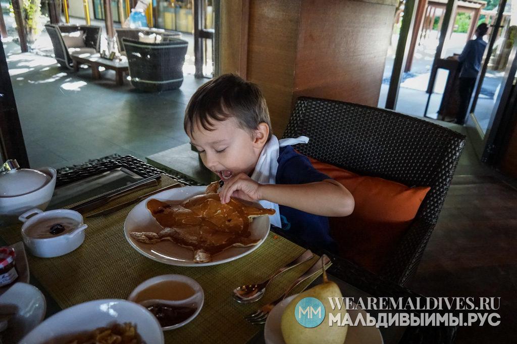 Ребенок ест блин в форме черпашки в ресторане Javvu отеля Shangri-La's Villingili