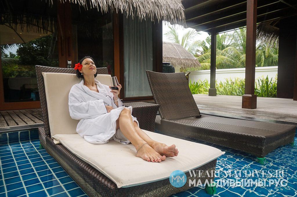 Девушка с бокалом вина на шезлонге в личном бассейне виллы отеля Shangri-La's Villingili